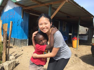 Jocy hugging a child in Kenya