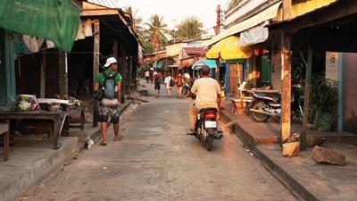 Local men walk down a road on King Island (Koh Sdach), Cambodia