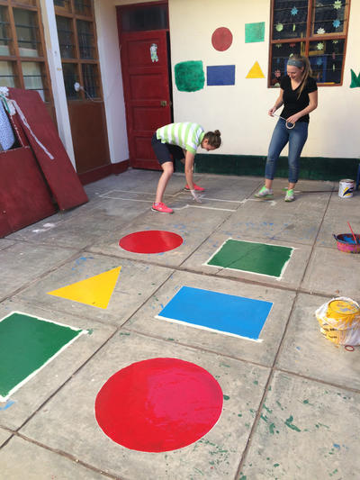 Painting shapes on the floor at a kindergarten in Peru