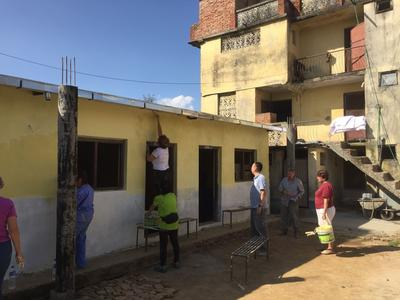 Older volunteers painting a local school