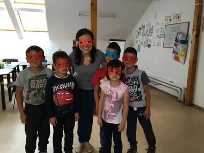 Katrina posing with Romanian children in the masks they made