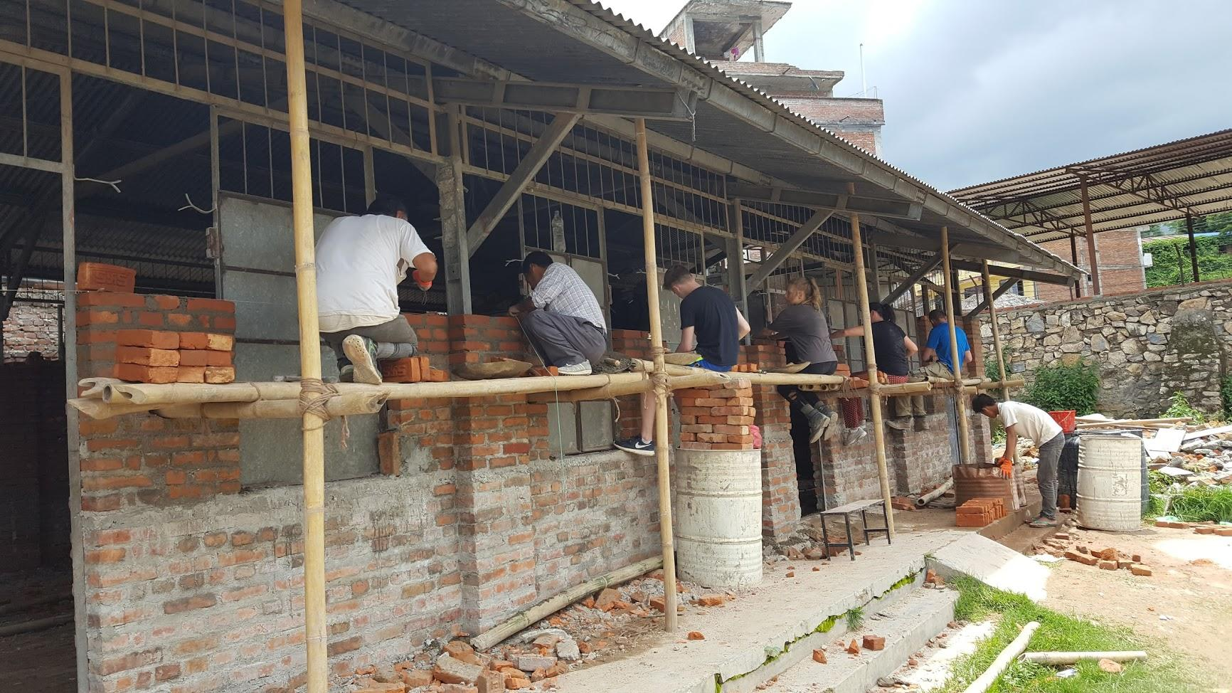 Building volunteers constructing the walls of a classroom in Nepal