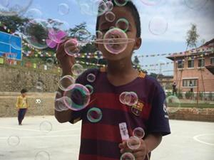 Young boy blowing bubbles at the care centre