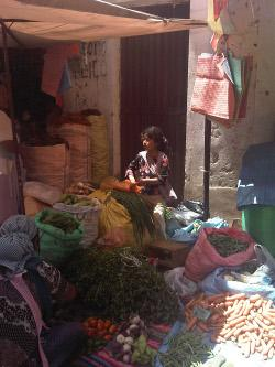 Quechuan girl with her produce at La Cancha market, Cochabamba