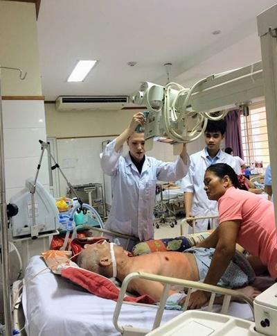 Medical volunteer in Vietnam assists staff with a patient