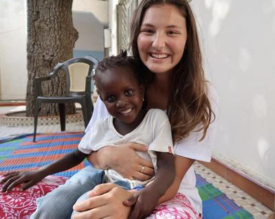 Maya with a young girl in Senegal