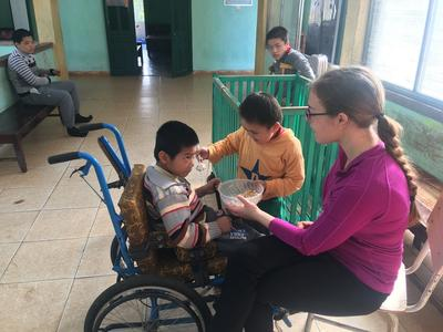 Naomi helps with feeding a child at a rehabilitation centre