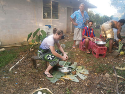 Volunteer helping to prepare food with host family in Samoa