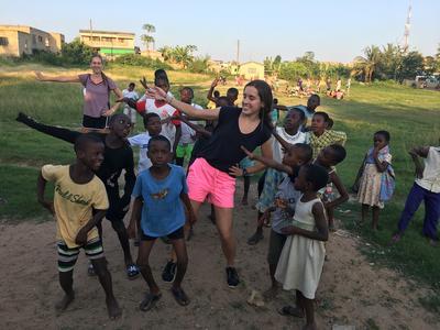 Volunteers and children dancing together