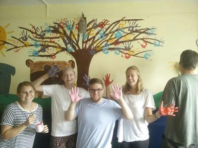 Volunteers painting an educational mural