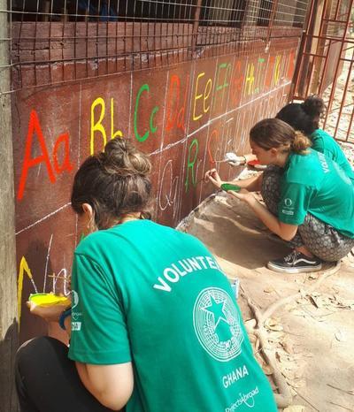 Volunteers painting a mural at a school in Ghana