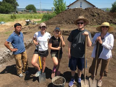 Archaeology volunteers pose for a photo on their dig site