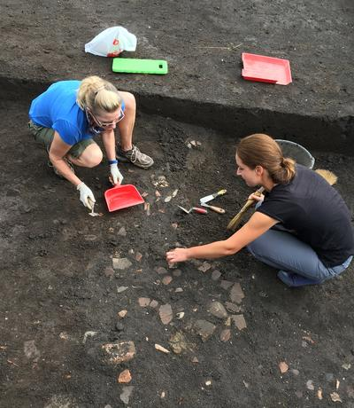 Volunteers carefully unearth artefacts at a dig site