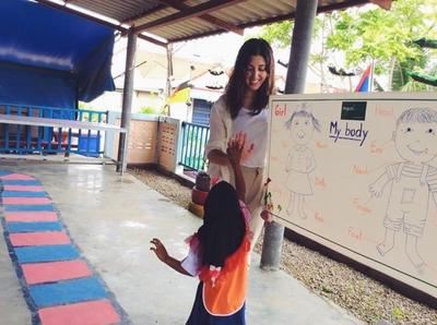 A volunteer and a child high five during a lesson