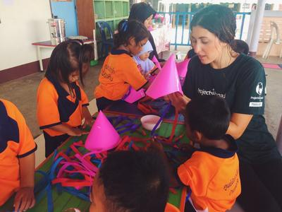 Volunteers run a crafts lesson with local children