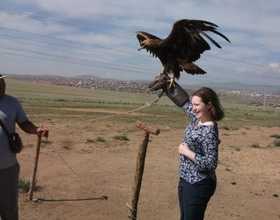 Volunteer holds a hunting eagle in Mongolia