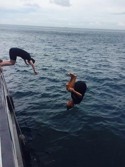 Volunteers doing somersaults off the side of the boat