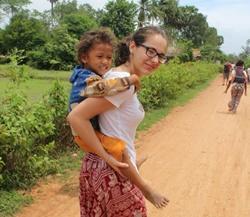 Voluntaria de Projects Abroad en Camboya cogiendo niño