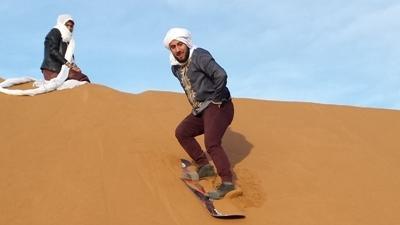 Un volontaire sur une planche de snowboard dans le désert marocain