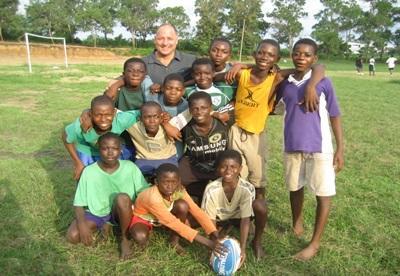 Nicolas Jones, coach anglais de rugby et volontaire de Projects Abroad entouré de jeunes rugbymen ghanéens
