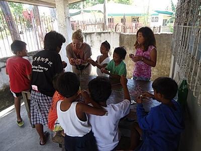 Valérie lors d'un atelier bracelets avec les enfants des rues