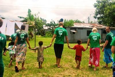 Frivillige og barn i lokalsamfunnet på Fiji rusler en tur