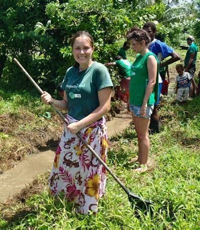 Rikke Mangor-Jensen raker i gresset på Natur- og Miljøprosjekt på Fiji