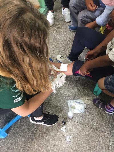 Wolontariuszka zakłada opatrunek na nodze pacjentki
