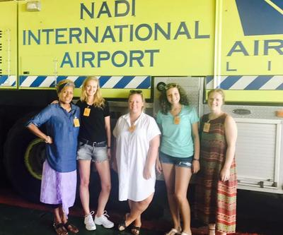 Michalina wraz z innymi wolontariuszkami pozują do zdjęcia na tle nazwy lotniska