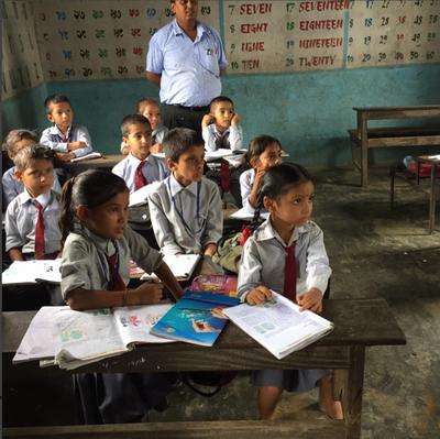 Dzieci z lokalnej szkoły uśmiechają się do zdjęcia
